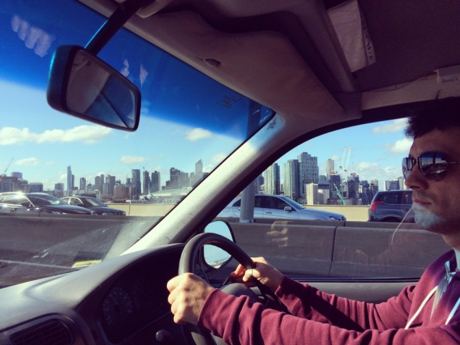 Campervan interior with driver and Melbourne city skyline