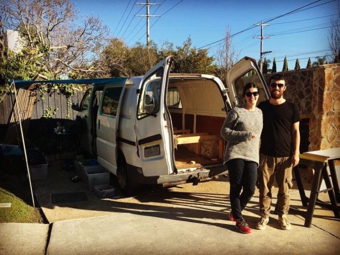 Travel couple in front of renovated campervan