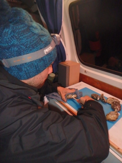 Gareth shucking oysters in the van
