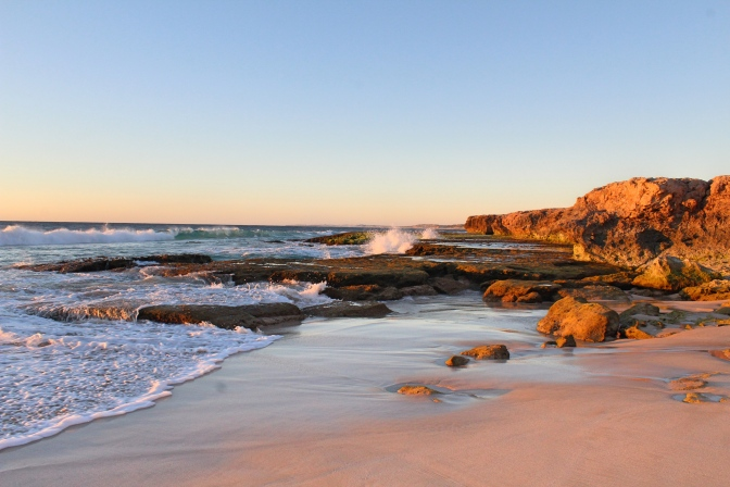 Sunset on rocky beach Red Bluff Western Australia