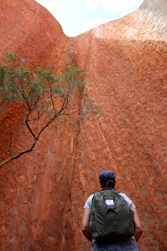 Looking up at Uluru rock face backpack Northern Territory